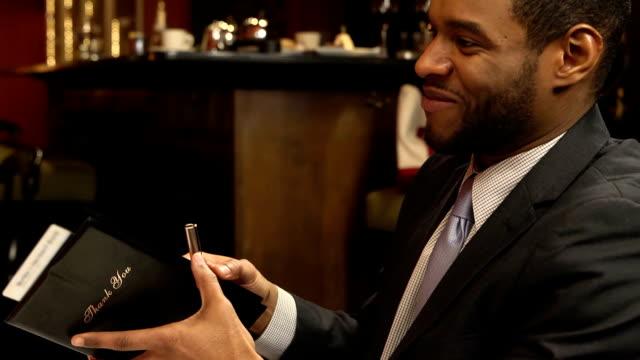 uomo firma fattura in affollato ristorante-primo piano - video di credit card video stock e b–roll