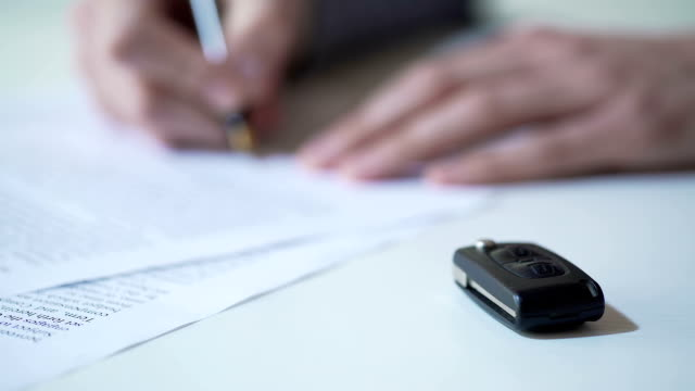 Man signs papers on car purchase or rent, auto insurance services, key on table