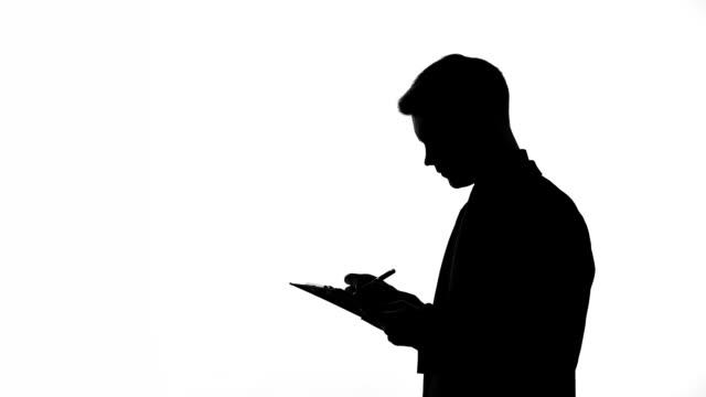 vídeos de stock, filmes e b-roll de silhueta de homem escrevendo respostas para questionário inquéritos estatísticos, folha - questionário