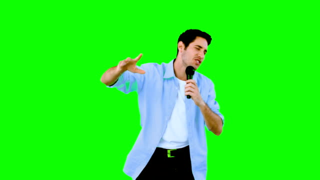 Man singing into microphone on green screen video