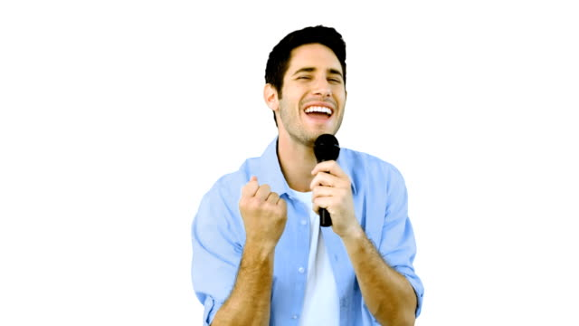 Man singing into microphone with emotion on white background video