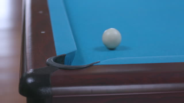 Man Sinking Final 8 Ball Shot in Corner Pocket on Blue Billiards Table