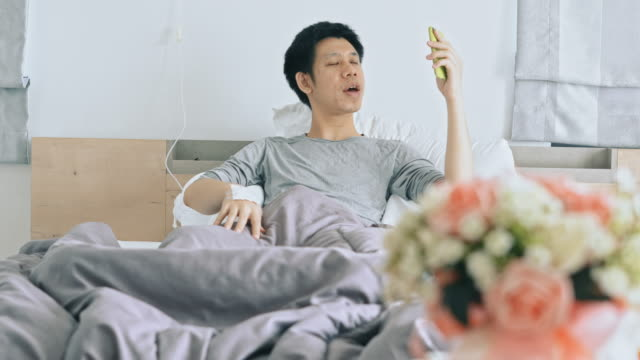 L'homme s'asseyez dans le lit après rétablissement de la maladie - Vidéo