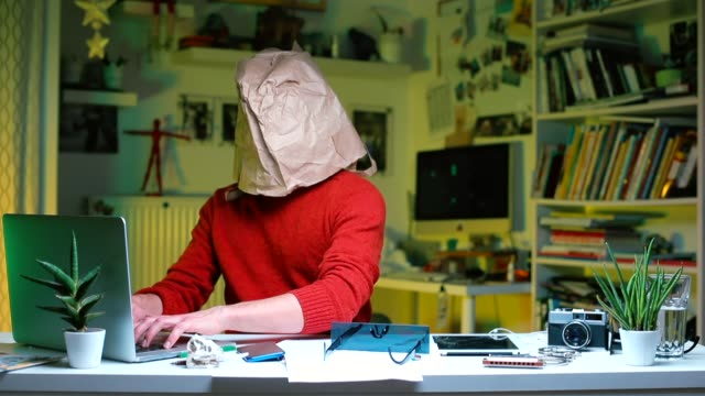 a man sits at an office desk with a paper bag on his head. - coprire video stock e b–roll