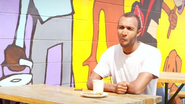 człowiek siedzi w kawiarni stół piknikowy i wygląda na czekać, fale na osobę - scone filmów i materiałów b-roll