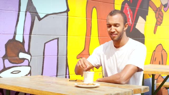 człowiek siedzi w odkrytym kawiarnia stół piknikowy w obecności tworzącego mural, kawy i napoje - scone filmów i materiałów b-roll
