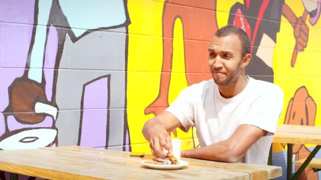 człowiek siedzi w odkrytym kawiarnia stół piknikowy w obecności tworzącego mural i zjada a scone - scone filmów i materiałów b-roll