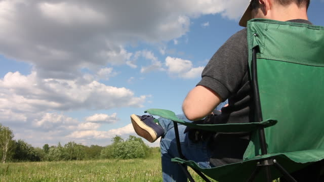 A man sits in a camping chair and photographs the landscape in front of him on the phone. Meadow with green grass. Blue sky with clouds.