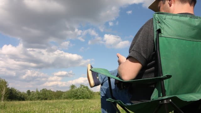 A man sits in a camping chair and speaks on the phone. Meadow with green grass. Blue sky with clouds.