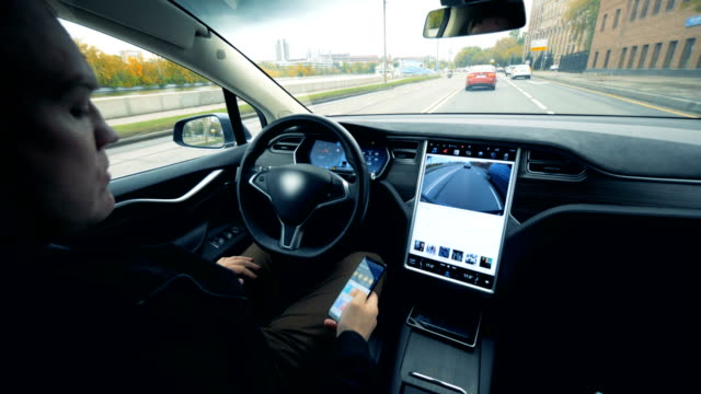 Man sits in an electric car going on autopilot. Futuristic automated electric car self driving.