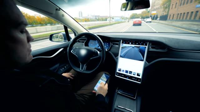 人坐在一輛自動駕駛儀上的電動車裡。未來自動電動車自動駕駛。 - 交通方式 個影片檔及 b 捲影像