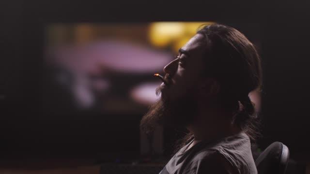 un uomo si siede davanti al monitor. accende una sigaretta e fuma pensierosamente. mo lento 4k - barba peluria del viso video stock e b–roll