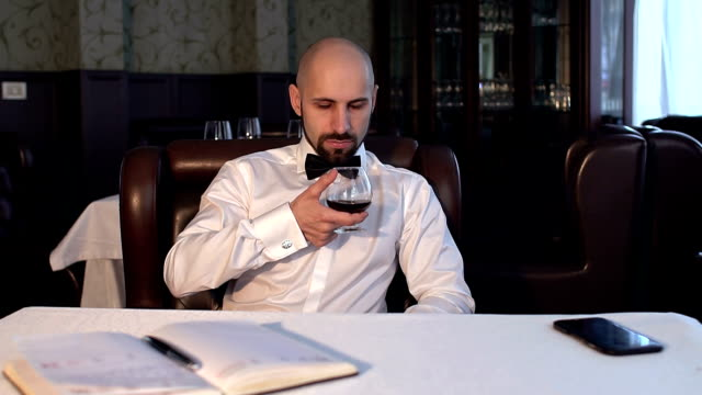 man sits in the restaurant with a glass of cognac. - scotch whisky video stock e b–roll