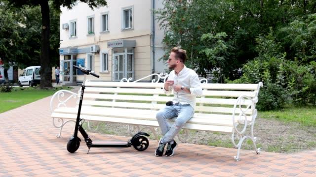 男はベンチに座っています。電動スクーターは近くに立っています。 - オルタナティブカルチャー点の映像素材/bロール