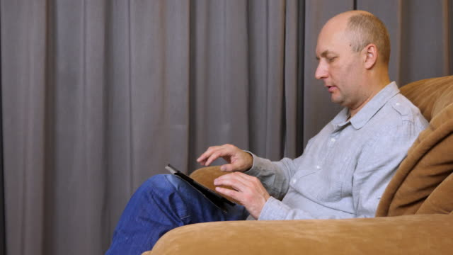 Man sits on armchair with tablet and speaks with somebody. video
