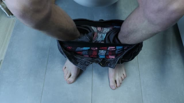 Man sits on toilet and drops toilet paper, close up view. Top view of male legs in jeans with bare feet sitting on toilet in grey bathroom.