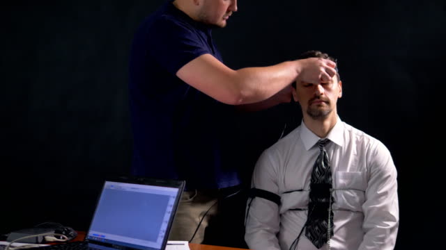 A man sitting and being prepared for polygraph test. 4k 60 fps. video