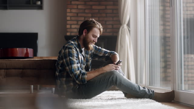 man sitting and using phone at livingroom - młodzi mężczyźni filmów i materiałów b-roll