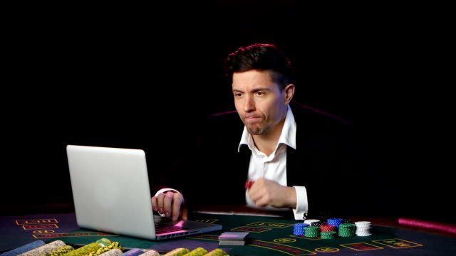 Man sitting at a laptop and playing at online casinos. Close up video