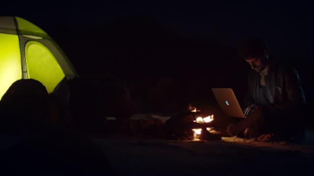 vidéos et rushes de homme assis sur le feu de camp avec son ordinateur portable - paysage extrême