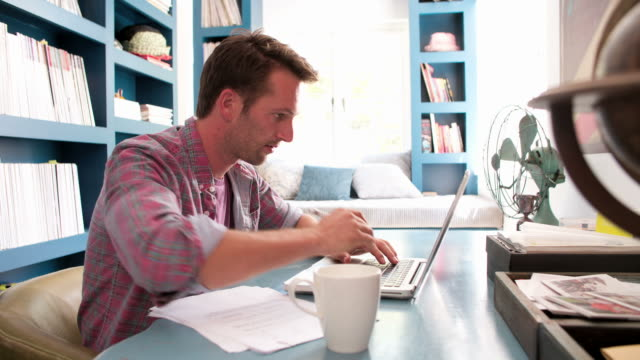 Man Sitting At Desk Working In Home Office video