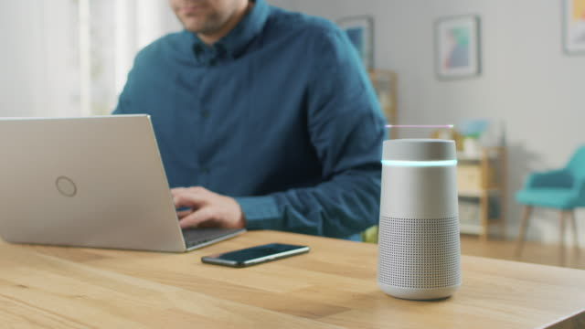 Video Man Sitting at His Desk Works on Laptop, Beside Him Smart Speaker with AI Assistance Answers Questions, Plays Music, Podcast. Animated Graphics of Voice Command Visualization Waveform