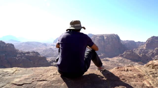 산 꼭대기에 앉아 멋진 전망, 요르단고대 도시 페트라의 절정, 여행자, 사람들 휴가, 여행 개념을 바라보는 남자 - mountain top 스톡 비디오 및 b-롤 화면