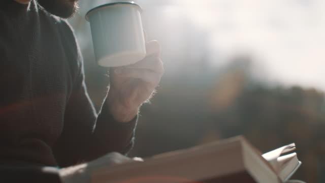 앉아, 커피를 마시고 캠핑에서 책 읽는 남자 - reading 스톡 비디오 및 b-롤 화면