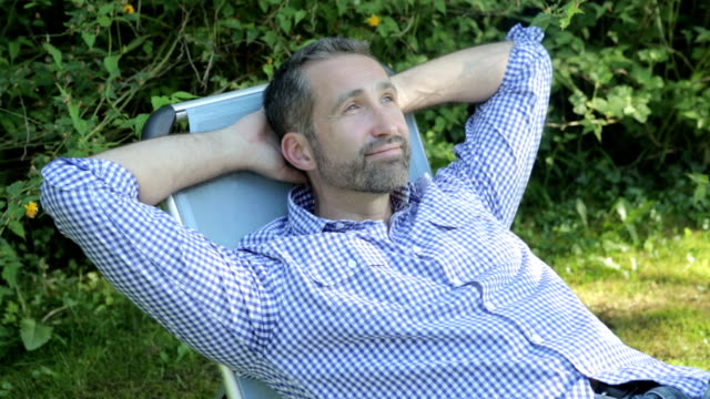 man sitting in a garden handsome man sitting in a chair in a garden and relaxes lounge chair stock videos & royalty-free footage