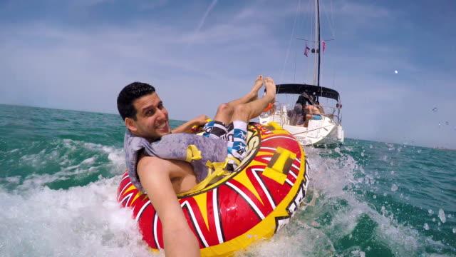 stockvideo's en b-roll-footage met man zit in opblaasbare ring gesleept door een boot in het water en het opnemen van zichzelf met de go pro camera - opblaasband