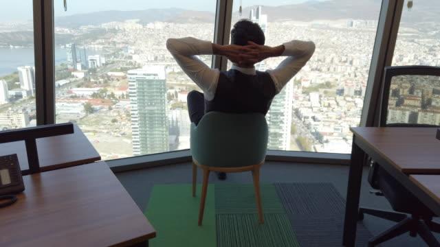 stockvideo's en b-roll-footage met man zittend in kantoor kijkt uit raam - comfortabel