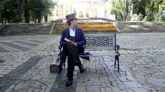 mannen sitter i parken och väntar kvinnan han älskar - ancient white background bildbanksvideor och videomaterial från bakom kulisserna