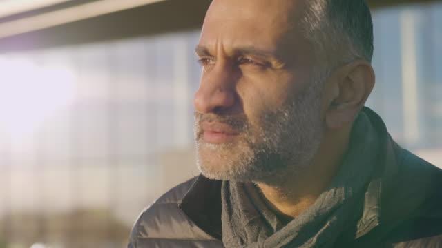 en man som sitter i solen överväger sitt arbete - människokroppsdel bildbanksvideor och videomaterial från bakom kulisserna