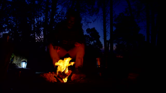 フォレスト 4 k でキャンプファイヤーの近くに座っている男 ビデオ
