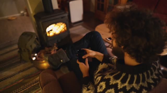 man sitting near wood stove  in cozy cabin and drinking tea - время дня стоковые видео и кадры b-roll