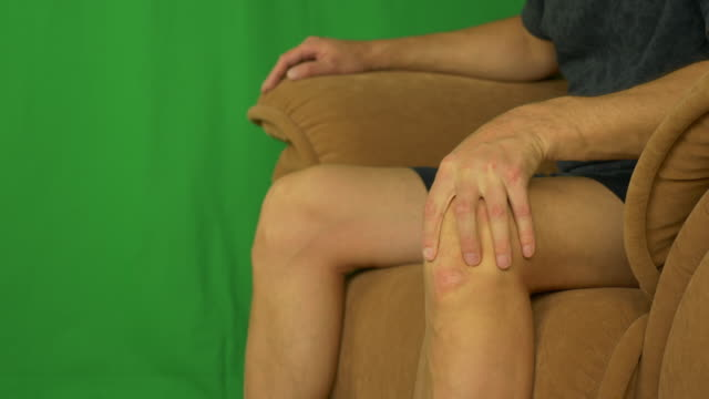 Man sitting on armchair and strocking his knee by palm hands. video