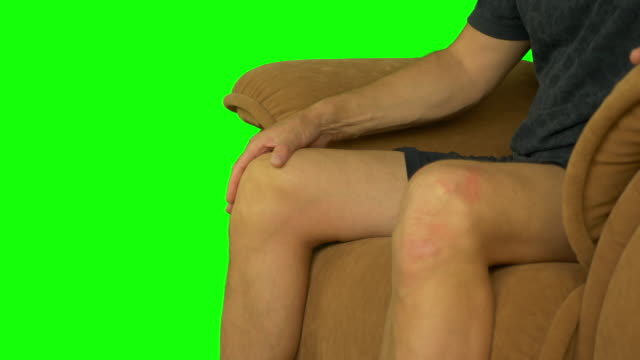 Man sitting on armchair and stroking his knee by palm hands. video