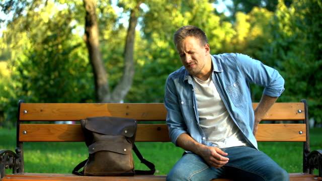 vídeos de stock, filmes e b-roll de homem que senta-se no banco que sofre da dor traseira do amante após o traumatismo ou ferimento - rim órgão interno