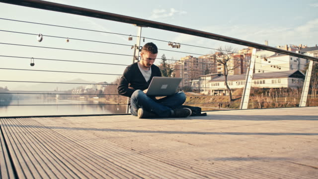 WS Man Sitting On Bridge And Using Laptop video