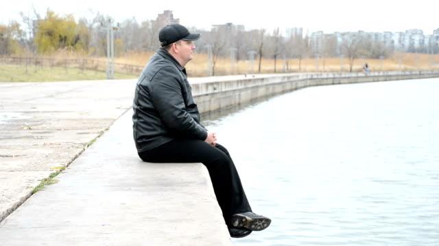 Man sitting on concrete slabs video