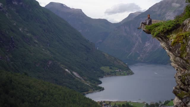 Man sitting on rock near Geirangerfjord in Norway