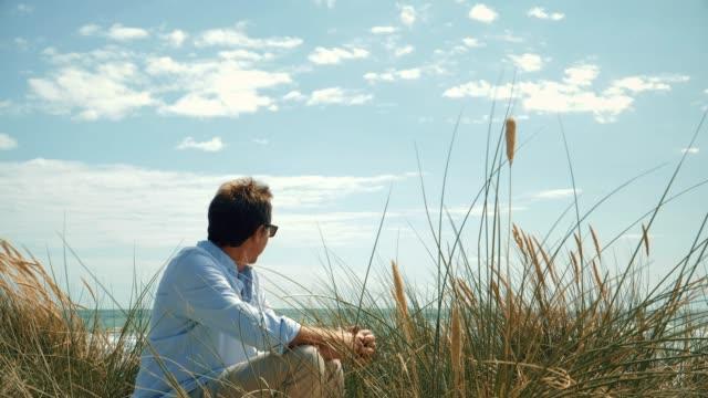man sitting on the beach sand dunes. - krajobraz morski filmów i materiałów b-roll