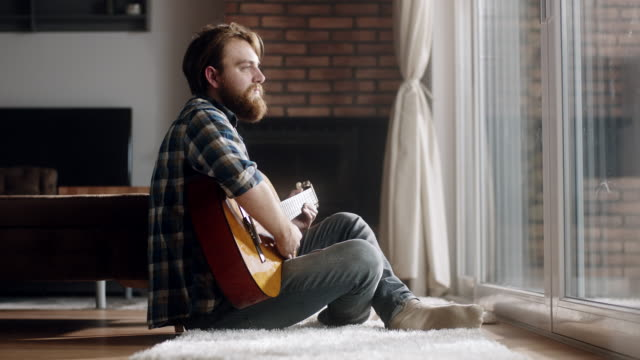 Man sitting on the floor and plays guitar at home Young man sitting on the floor and plays guitar at home guitar stock videos & royalty-free footage