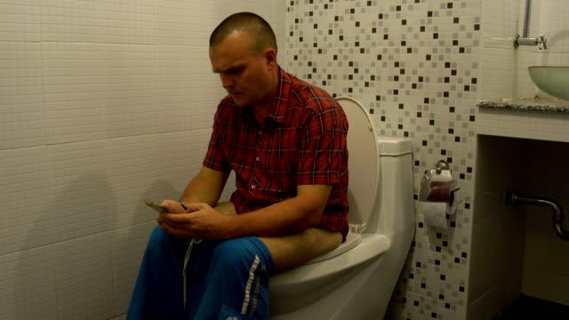 stockvideo's en b-roll-footage met een man zittend op het toilet en gebruik een smartphone - cell phone toilet