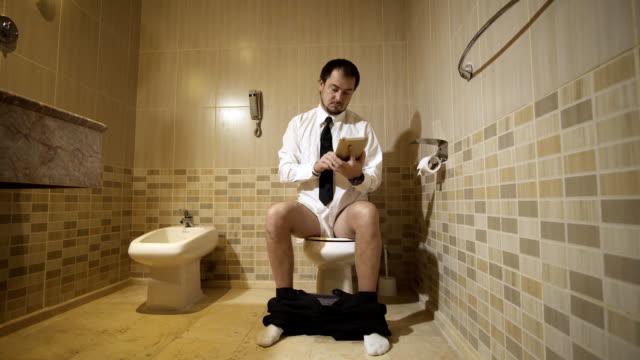 stockvideo's en b-roll-footage met een man zittend op het toilet in een luxe toilet met een telefoon en werken. fullhd - cell phone toilet