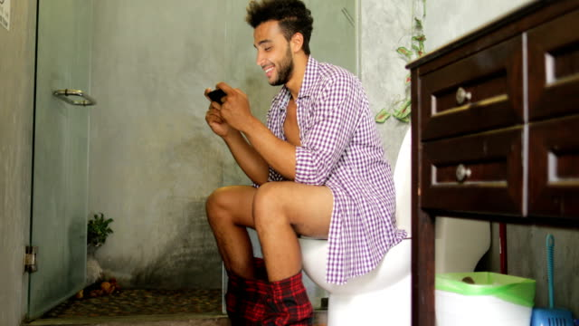 Man Sitting On Toilet Use Cell Smart Phone Young Latin Guy Playing Game video