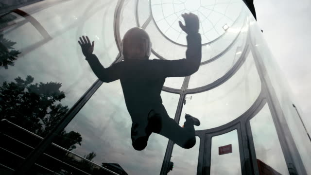 Man skydiver flies in a circle in wind tunnel. Flying in a wind tunnel video