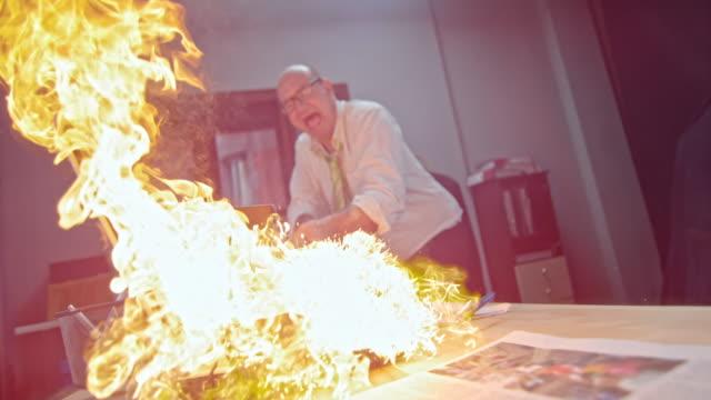 SLO MO Man slamming the burning laptop with hammer