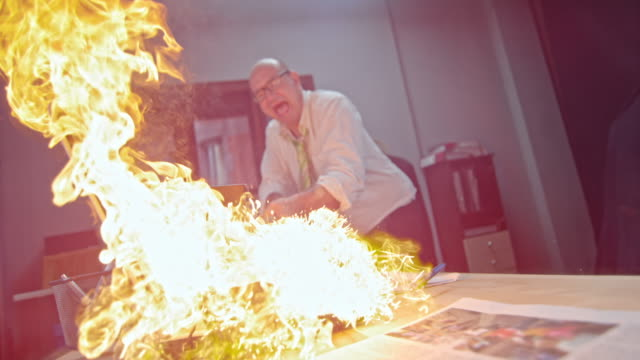 SLO MO Man slamming the burning laptop with hammer Slow motion medium locked down shot of a business man slamming a mallet at the burning laptop on the office desk. breaking stock videos & royalty-free footage