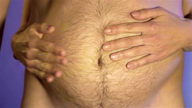 Man slår händerna mot kvinnans mage och vågor av subkutant fett sprids ut slow motion. Begreppet hälsosam mat och livsstil video